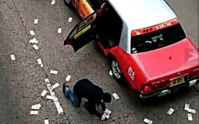 A man picks up money spilled by a security van in Wan Chai on December 24. More than HK$7 million is still missing. Photo: SCMP Pictures