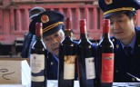 Policemen inspect seized bottles of fake wine. A Jiangxi restaurant owner was made to compensate a diner after he sold the man counterfeit liquor. Photo: Reuters