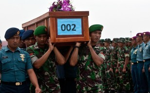 Indonesian military forces carry a victim's coffin. Photo: AFP