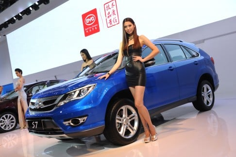 Models pose next to the BYD S7 SUV at the Shanghai Auto Show in 2013. Photo: AFP