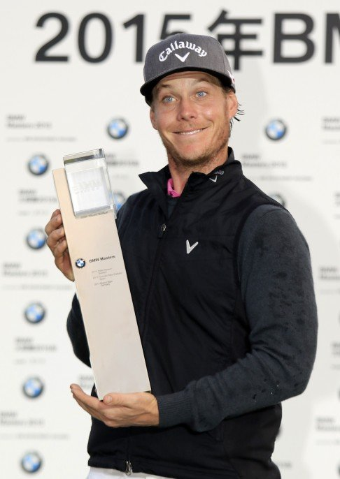 Sweden s Kristoffer Broberg can t contain his delight as he shows off the  trophy for winning the BMW Masters. Photo  AP.