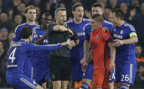 Referee Bjorn Kuipers is surrounded by Chelsea players before a red card is issued to PSG's Zlatan Ibrahimovic. Photo: AP