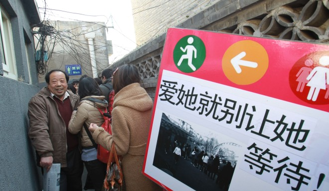 Female university students hold a banner with the slogan 'If you love her, do not let her wait in line', at a men's toilet during the 'Occupy Men's Toilets' campaign in Beijing February 26, 2012.