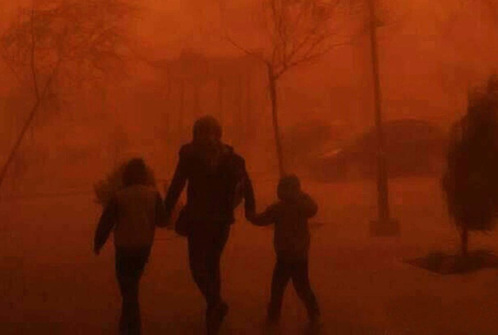 People walk through a sandstorm shrouding Beijing in dust. Photo: SCMP Pictures